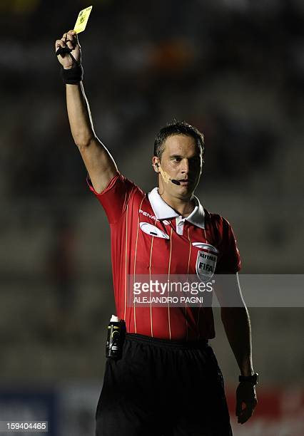 Argentinian referee Patricio Loustau shows a yellow card during their South American U-20 Championship Group B football match between Uruguay and...