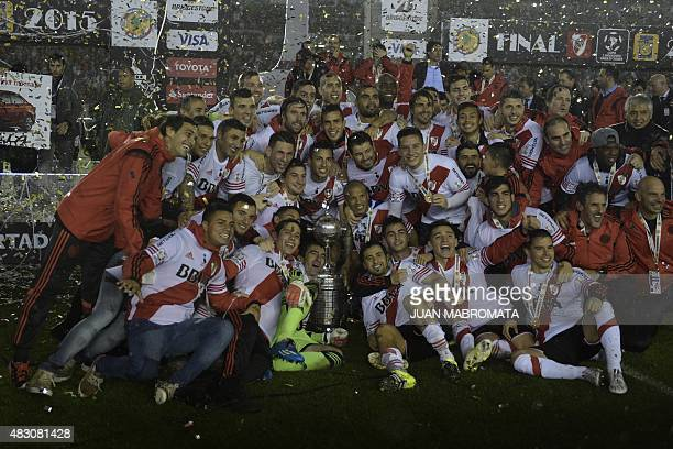 Argentinian River Plate players pose with the Libertadores Cup trophy after winning the second leg final match against Mexican Tigres by 30 at...