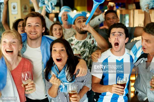 argentinian soccer fans watching match together at pub - internationaal voetbalevenement stockfoto's en -beelden