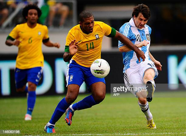 Argentinian soccer player Lionel Messi scores his third third goal past Brazil's Juan during a friendly match at the MetLife Stadium in East...