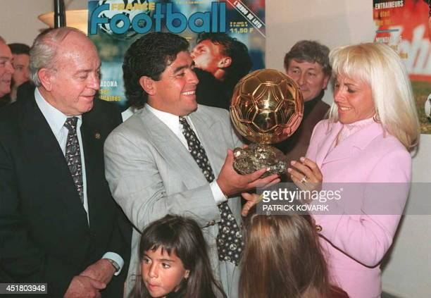 Argentinian soccer star Diego Maradona hands the honorary Ballon d'Or award he received 03 January to his wife Claudia as former soccer great Alfredo...