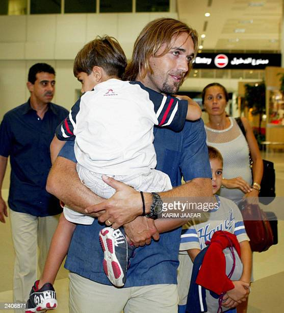 Argentinian soccer star Gabriel Batistuta carries his son as he arrives in Doha with his family 16 August 2003 The 34yearold Batistuta also known as...