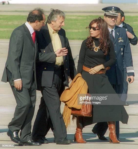 Argentinian vice President Daniel Scioli President Nestor Kirchner and wife Cristina Fernandez de Kirchner speak before boarding on presidential...