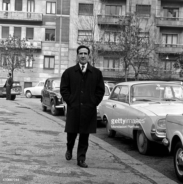 Argentinianborn French football trainer Helenio Herrera walks along a sidewalk with his hands in pocket beside some parked cars he nicknamed The...