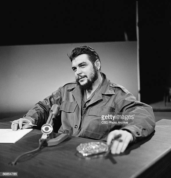 Argentinianborn Marxist revolutionary Ernesto Che Guevara Cuban Minister of Industry dressed in military fatigues smokes a cigar and appears on the...
