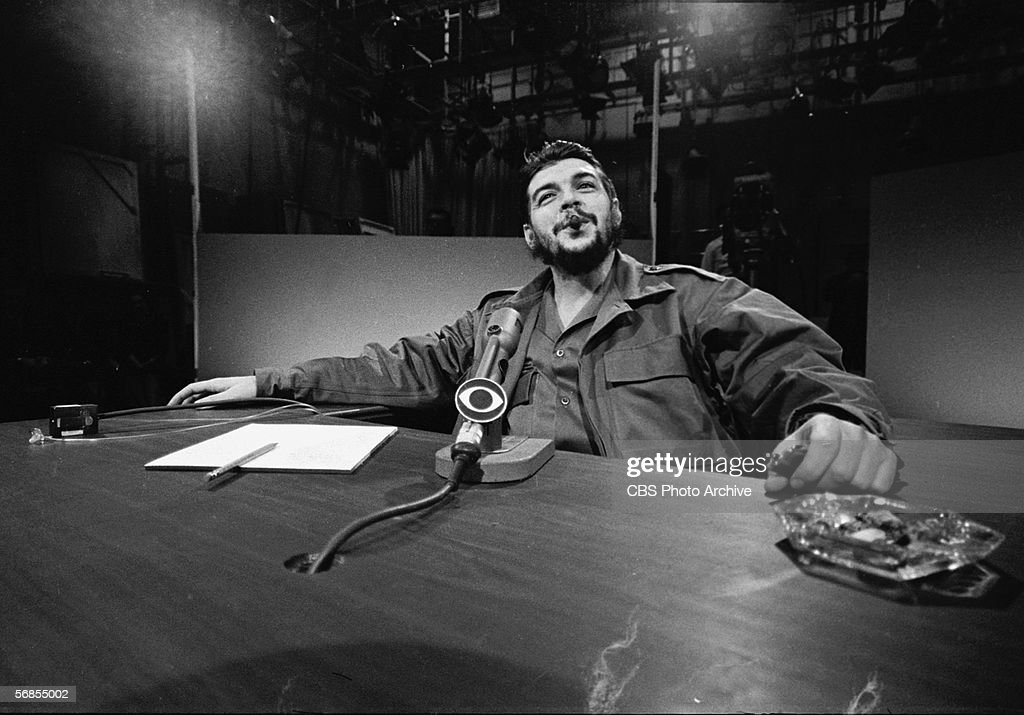 Argentinian-born Marxist revolutionary Ernesto Che Guevara (1928 - 1967), Cuban Minister of Industry, dressed in military fatigues and smoking a cigar, reclines in his chair as he appears on the CBS current affairs program 'Face the Nation,' New York, New York, December 14, 1964. The television studio set is visible behind him.