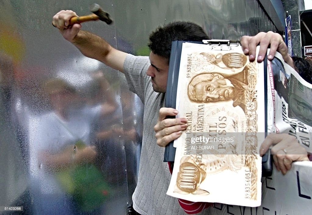 Argentinians try to break down a metal wall at a b : News Photo