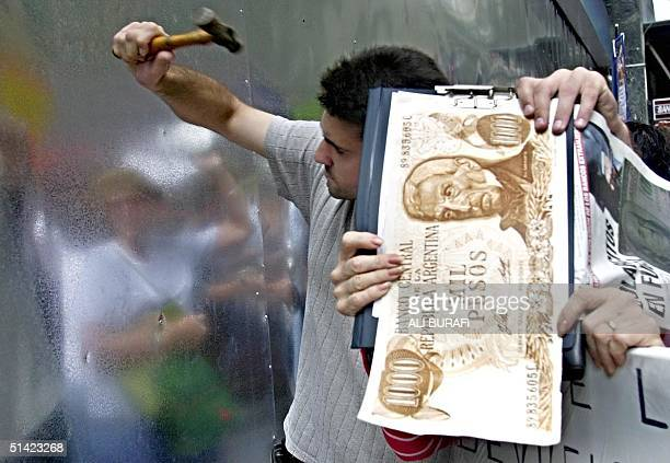 Argentinians try to break down a metal wall at a bank 18 February 2002 in Buenos Aires in protest by the blockade of their savings imposed by the...