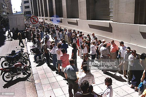 Argentinians wait in a long line in front of the Banco de la Nacion Argentina for their turn to buy dollars 01 February 2002 in Buenos Aires...
