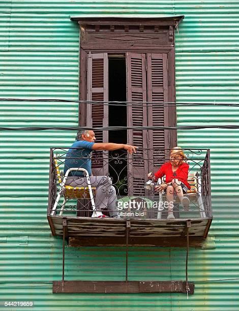 Ehepaar auf dem Balkon vor einer grünen Hausfassade im Stadtviertel La Boca
