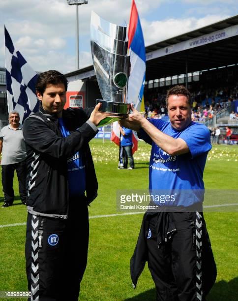 Argirios Giannikis and Coach Markus Kauczinski of Karlsruhe lift the trophy after third Bundesliga match between SV Wehen Wiesbaden and Karlsruher SC...