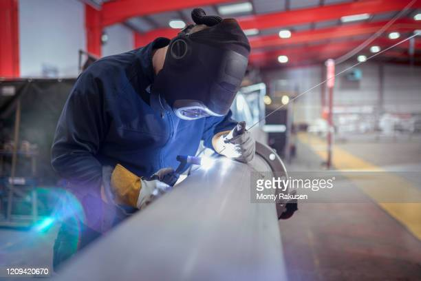 argon welder welding pipe in metal fabrication factory. - pipe stock pictures, royalty-free photos & images