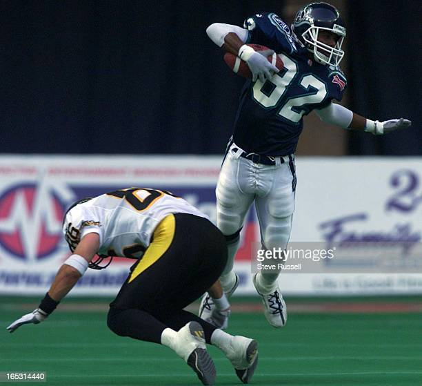 Ted Alford of the Toronto Argonauts avoids a tackle from the Hamilton Ti-cats Trevor Shaw in Toronto, Ontario, July 20 2001.
