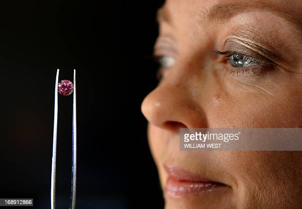 Argyle Pink Diamonds manager Josephine Johnson inspects the biggest 'red' diamond produced by mining giant Rio Tinto's Australian mine and which is...