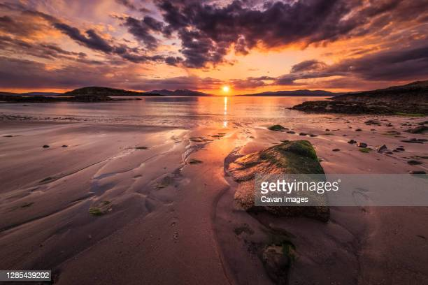 argyll beach sunset with foreground rock - vista marina fotografías e imágenes de stock