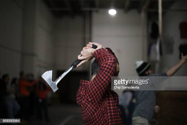 Ari Evans prepares to throw a hatchet at a wood target wall at Bad Axe Throwing March 28 2018 in Washington DC Evans and fellow Capitol One employees...