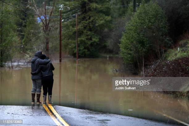 Ari Herman and Lea Herman embrace as they look at a flooded section of highway 116 on February 27 2019 in Guerneville California The Russian River...