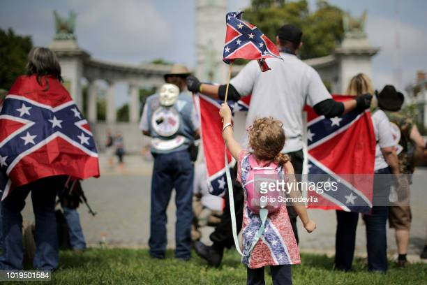 Aria Berry waves a Confederate battle flag as she joins her father and about 20 members and supporters of confederate heritage groups including CSA...