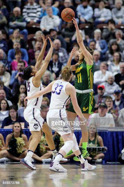 Ariadna Pujol of the South Florida Bulls passes while defended by Gabby Williams of the Connecticut Huskies and Katie Lou Samuelson of the...