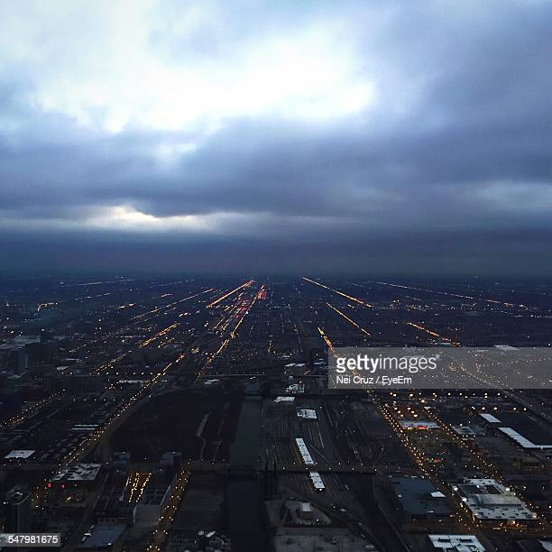 Arial View Of Illuminated Cityscape Against Cloudy Sky