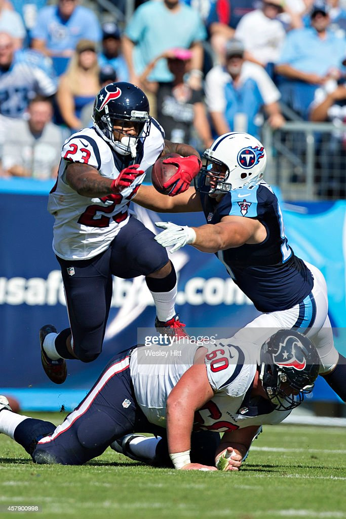 Arian Foster #23 jumps Ben Jones #60 of the Houston Texans while he runs the ball against the Tennessee Titans at LP Field on October 26, 2014 in Nashville, Tennessee. The Texans defeated the Titans 30-16.