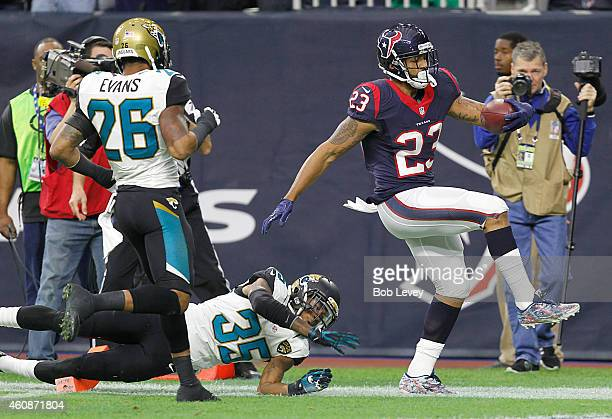 Arian Foster of the Houston Texans catches a touchdown pass against Demetrius McCray and Josh Evans of the Jacksonville Jaguars in a NFL game on...