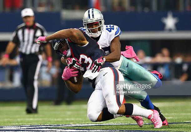 Arian Foster of the Houston Texans is tackled by Barry Church of the Dallas Cowboys in overtime at ATT Stadium on October 5 2014 in Arlington Texas
