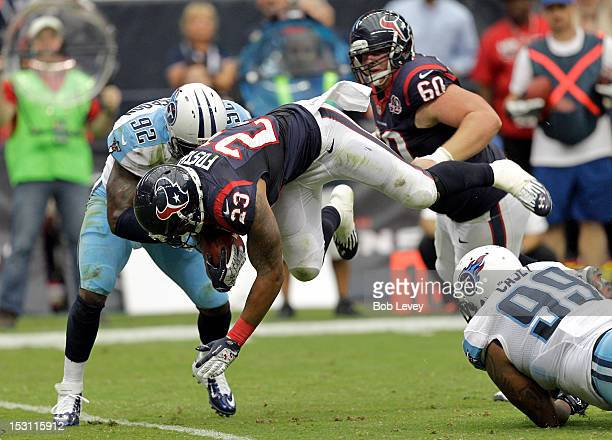 Arian Foster of the Houston Texans leaps over Jurrell Casey of the Tennessee Titans as he is tackled by Will Witherspoon of the Tennessee Titans at...