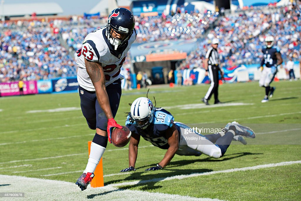 Arian Foster #23 of the Houston Texans scores a touchdown around Michael Griffin #33 of the Tennessee Titans at LP Field on October 26, 2014 in Nashville, Tennessee. The Texans defeated the Titans 30-16.