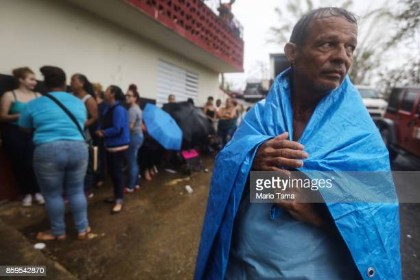 Arian Rodriguez covers himself with a tarp as residents wait in the rain to register with FEMA more than two weeks after Hurricane Maria hit the...