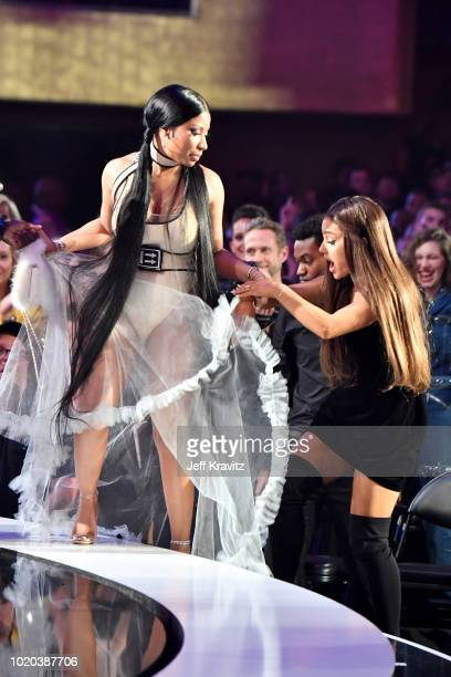 Ariana Grande helps Nicki Minaj onstage as she accepts the award for 'Best Hip Hop Video' during the 2018 MTV Video Music Awards at Radio City Music...