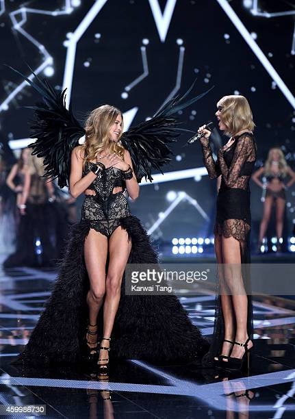 Ariana Grande performs as Doutzen Kroes walks the runway at the annual Victoria's Secret fashion show at Earls Court on December 2 2014 in London...