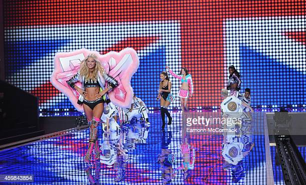 Ariana Grande performs as models walk the runway at the annual Victoria's Secret fashion show at Earls Court on December 2 2014 in London England