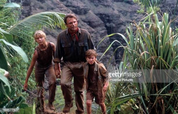 Ariana Richards walks with Sam Neill and Joseph Mazzello in a scene from the film 'Jurassic Park' 1993
