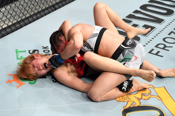Ariane Carnelossi of Brazil punches Liang Na of China in their women's strawweight bout during the UFC 261 event at VyStar Veterans Memorial Arena on...