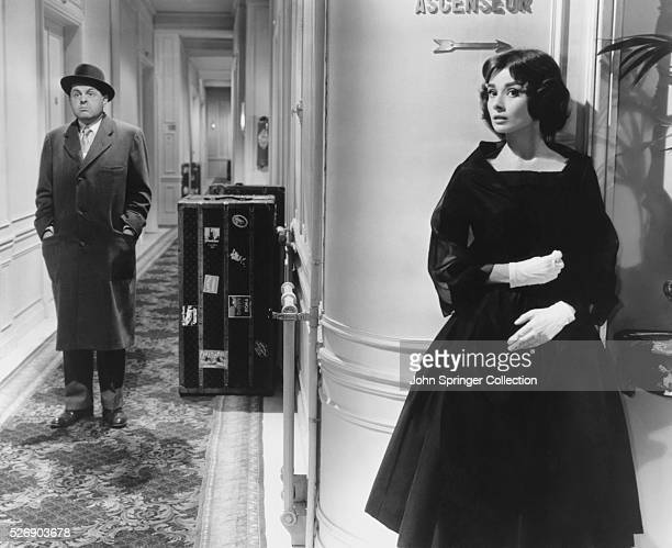 Ariane Chavasse hides around a hallway corner from Monsieur X John McGiver in a scene from the 1957 comedic romance Love in the Afternoon