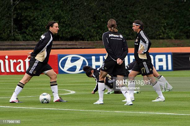 Ariane Hingst Kerstin Garefrekes are stretchingl during the Germany Women national team training session at Eisenbrand stadium on June 21 2011 in...