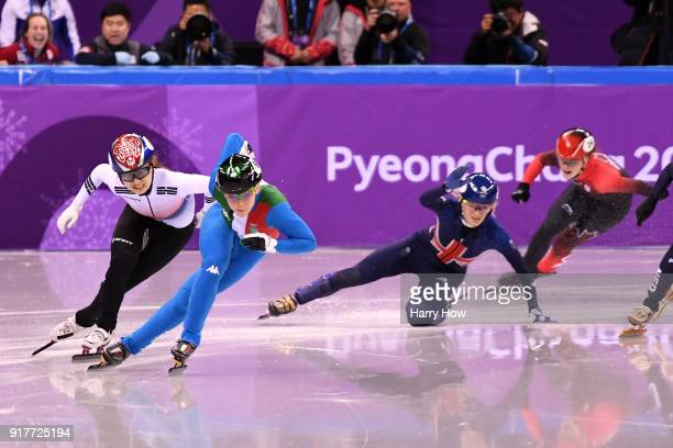 Arianna Fontana of Italy and Minjeong Choi of Korea race past as Elise Christie of Great Britain falls during the Ladies' 500m Short Track Speed...
