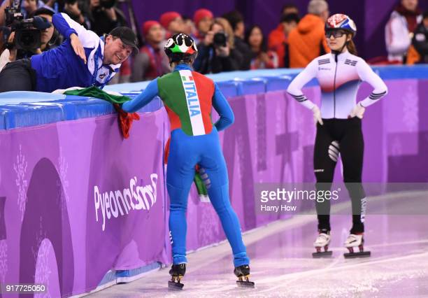 Arianna Fontana of Italy celebrates with her coach after winning the gold medal as Minjeong Choi of Korea looks on in the Ladies' 500m Short Track...