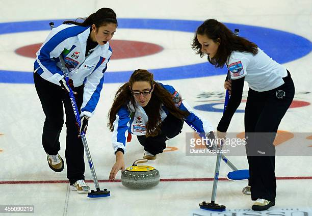 Arianna Losano of Italy and team mate Martina Bronsino sweep after Veronica Zappone throws a rock during the Olympic Qualification Tournament match...