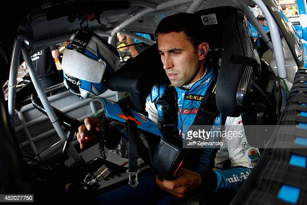 Aric Almirola, driver of the Charter Ford, sits in his car in the garage area during practice for the NASCAR Sprint Cup Series Camping World RV Sales...