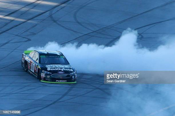 Aric Almirola driver of the Smithfield Bacon for Life Ford celebrates with a burnout after winning the Monster Energy NASCAR Cup Series 1000Bulbscom...