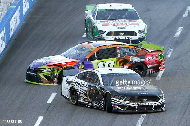 Aric Almirola, driver of the Smithfield Ford, and Kyle Busch, driver of the M&M's Halloween Toyota, are involved in an on-track incident during the...