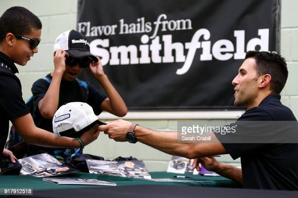 Aric Almirola driver of the Smithfield Ford Fusion for StewartHaas Racing in the Monster Energy NASCAR Cup Series signs autographs for honorroll...