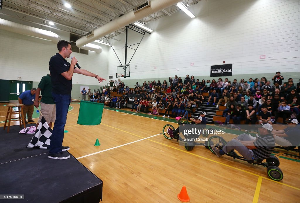 Aric Almirola, driver of the #10 Smithfield Ford Fusion for Stewart-Haas Racing in the Monster Energy NASCAR Cup Series, officiates a tricycle race with Principal Pablo Gallego and honor-roll students at Pierce Middle School on February 13, 2018 in Tampa, Florida.