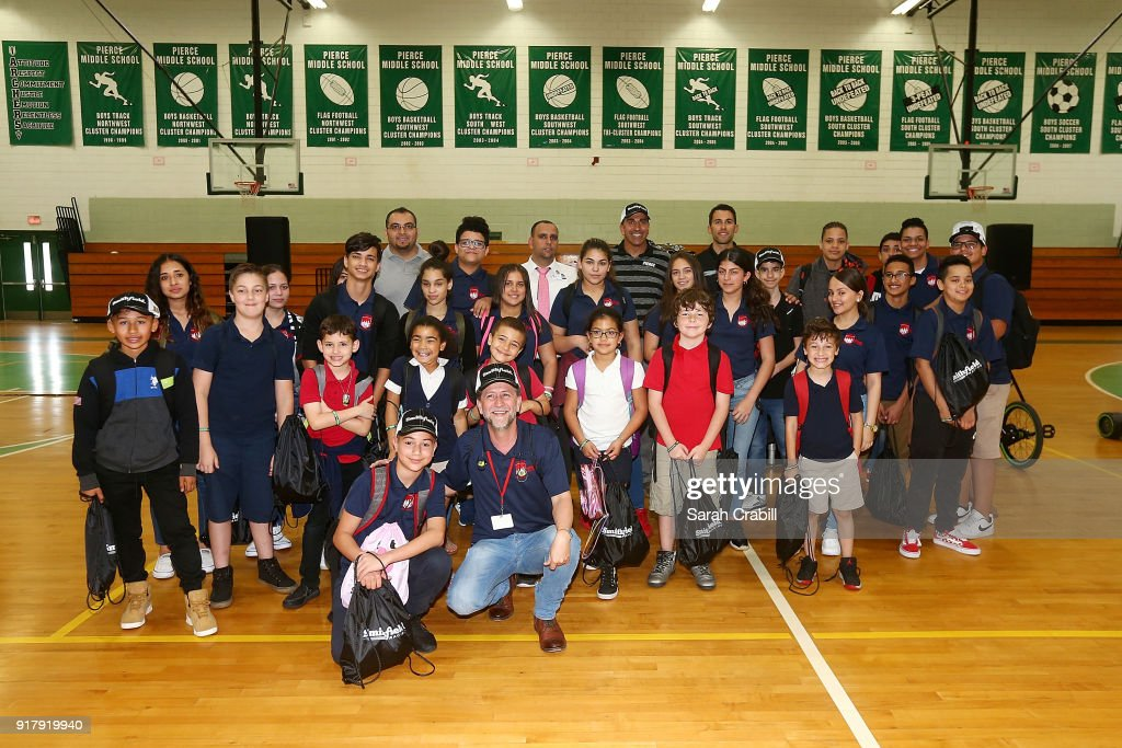 Aric Almirola, driver of the #10 Smithfield Ford Fusion for Stewart-Haas Racing in the Monster Energy NASCAR Cup Series, and honor-roll students pose for a photo at Pierce Middle School on February 13, 2018 in Tampa, Florida.