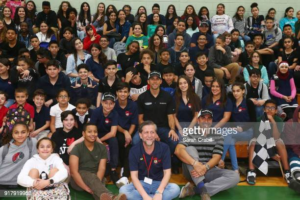 Aric Almirola driver of the Smithfield Ford Fusion for StewartHaas Racing in the Monster Energy NASCAR Cup Series and honorroll students pose for a...