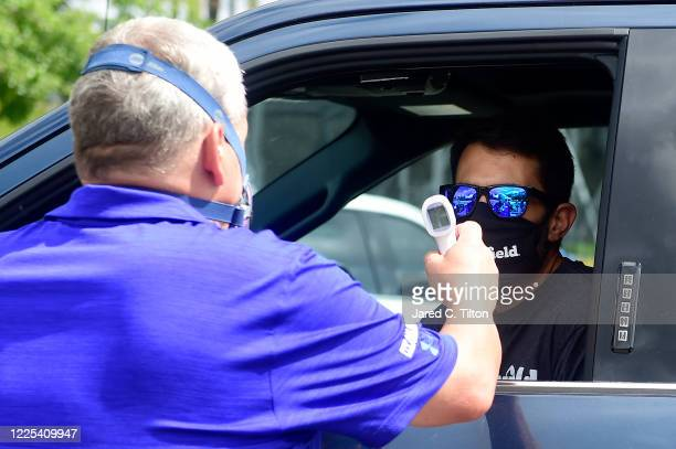 Aric Almirola driver of the Smithfield Ford has his temperature checked by NASCAR Security prior to the NASCAR Cup Series The Real Heroes 400 at...
