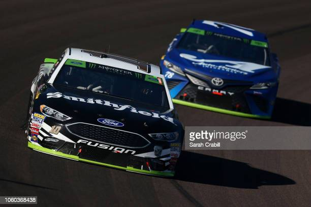 Aric Almirola driver of the Smithfield Ford leads Martin Truex Jr driver of the AutoOwners Insurance Toyota during the Monster Energy NASCAR Cup...