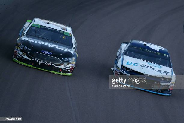 Aric Almirola driver of the Smithfield Ford races Kyle Larson driver of the DC Solar Chevrolet during the Monster Energy NASCAR Cup Series CanAm 500...